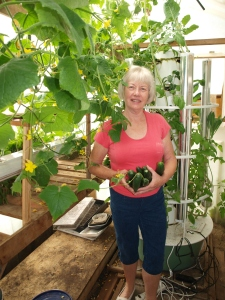 Linda Woolsey holding Zucchini see just picked from her Tower Garden.