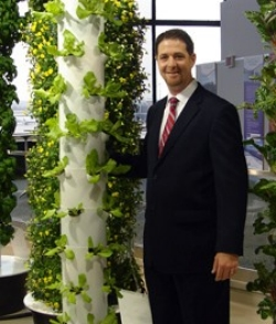 Photo of Tim Blank standing beside a Tower Garden.